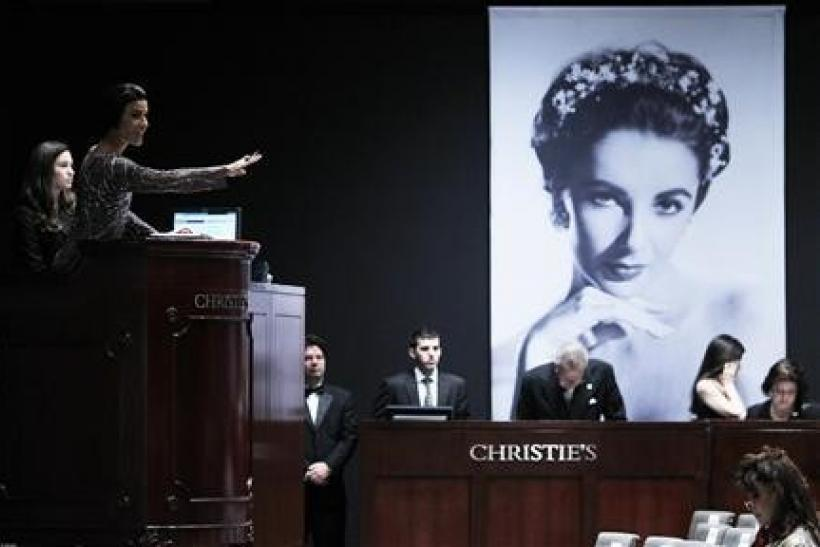 Christie's auctioneer Andrea Fiuczynski conducts an auction of Elizabeth Taylor's jewelry, clothing, art and memorabilia, near an image of the late actress at Christie's auction house in New York