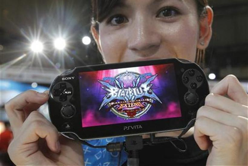 A promotional woman shows a Sony's PlayStation Vita handheld gaming device at Tokyo Game Show in Chiba