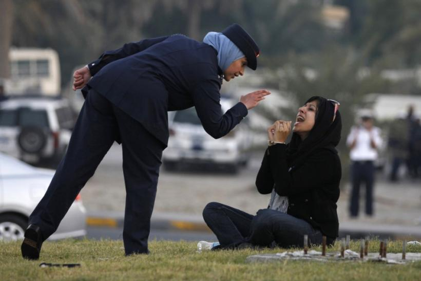 A police officer speaks to Zaynab al-Khawaja, daughter of Human Rights activist, Abdulhadi al-Khawaja, after she refused to leave after a sit-in in Manama