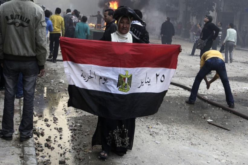 A protester carries her national flag during clashes with troops in Cairo
