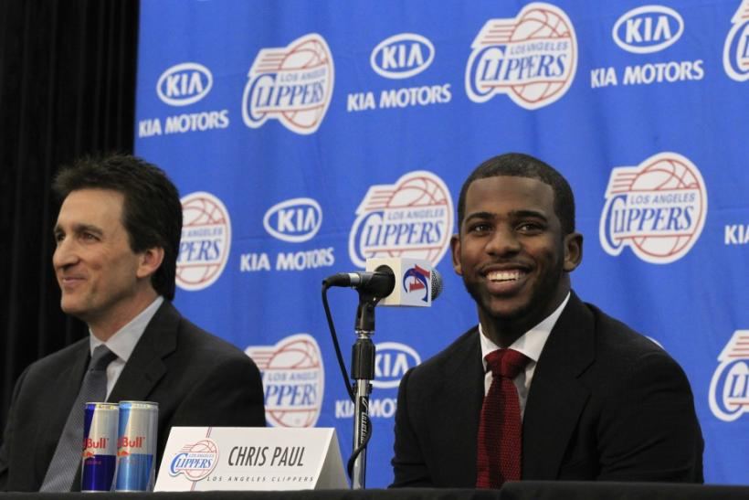 Los Angeles Clippers point guard Chris Paul (R) smiles as he sits with coach Vinny Del Negro during a news conference in Playa Vista, Los Angeles, California