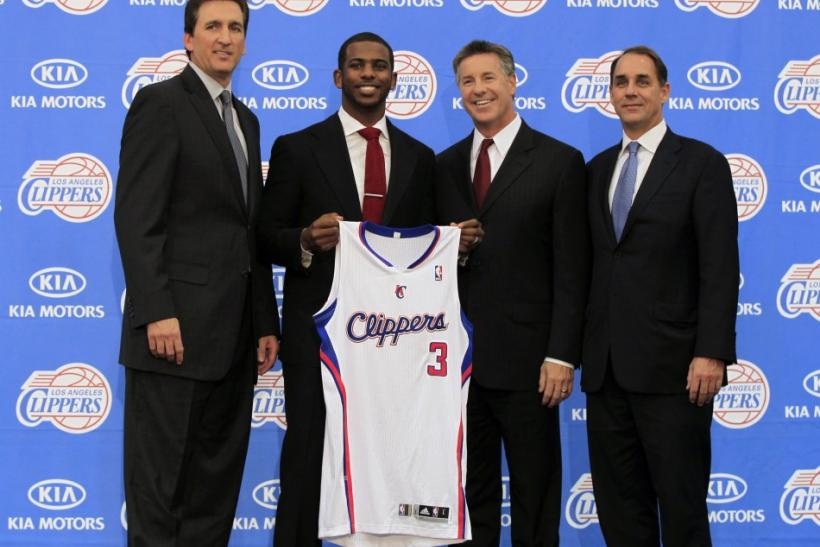 Los Angeles Clippers point guard Chris Paul (2nd L) poses with his new jersey as he stands with (L-R) Clippers Head Coach Vinny Del Negro, Vice President of Basketball Operations for the Clippers, Neil Olshey, and President of the National Basketball Asso