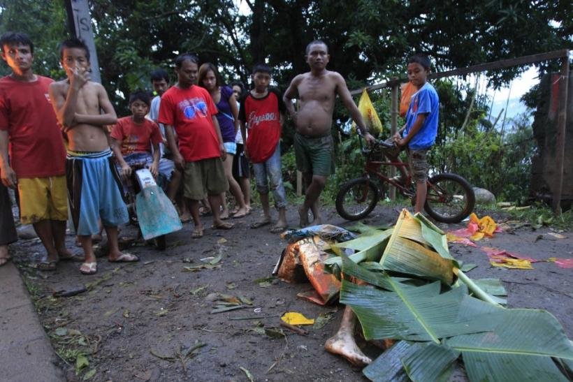 Residents gather near the body of a resident recovered from flashfloods caused by typhoon Washi in Balulang village in Cagayan de Oro