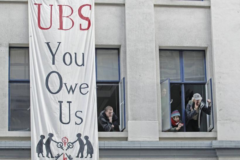 Protesters from the Occupy movement stand at the windows of one of several buildings in a quadrangle owned by banking giant UBS in the financial district City of London November 18, 2011.