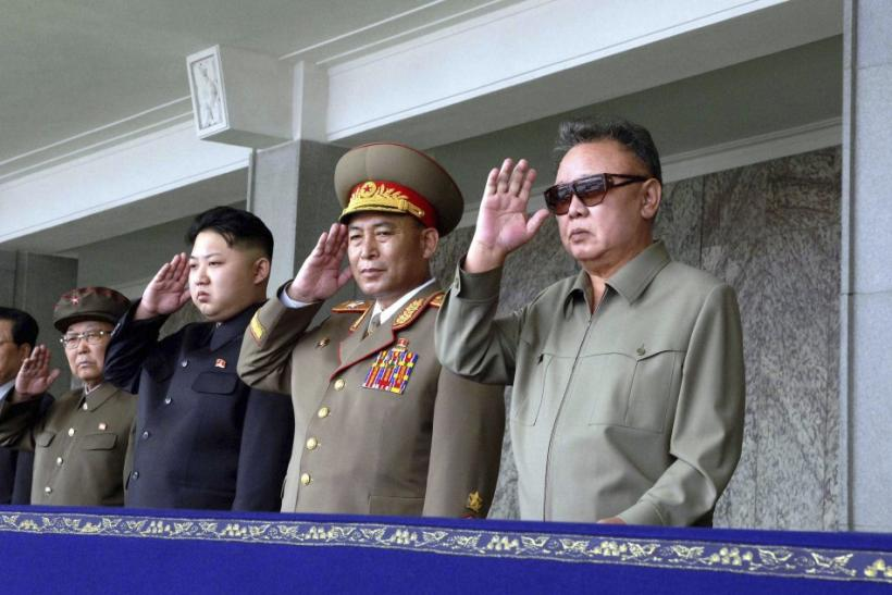 Kim Jong-il and his son Kim Jong-un salute as they watch soldiers attending a military parade