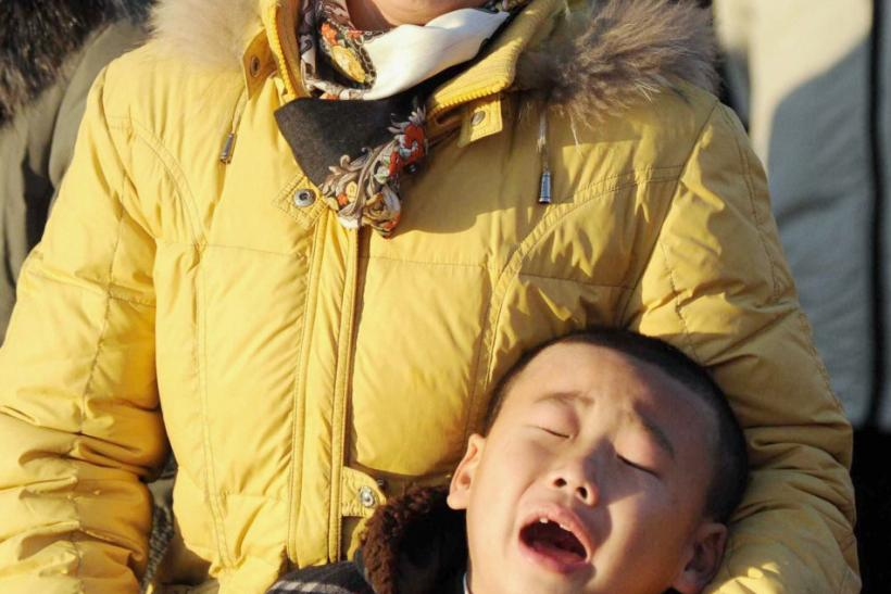 A woman and her son cry as they mourn the death of North Korean leader Kim Jong-il at a square on Mansu Hill in Pyongyang