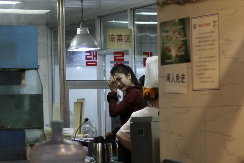 A waitress cries after hearing news of the death of North Korean leader Kim Jong-il, at a North Korean restaurant in Beijing