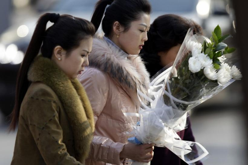 A North Korean woman holding flowers and other people arrive at the North Korea embassy to mourn the death of North Korean leader Kim Jong-il, in Beijing