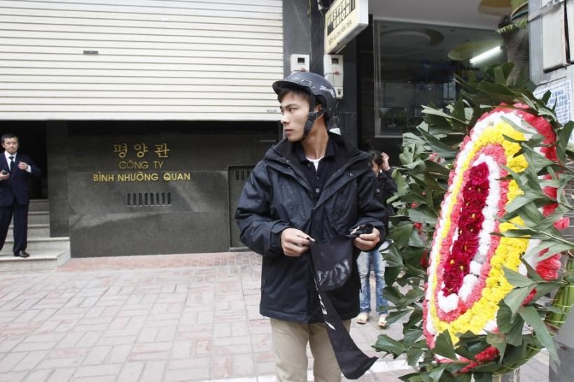 A North Korean man (L) gestures as a Vietnamese man (R) places a funeral wreath in front of Pyongyang Restaurant in Hanoi