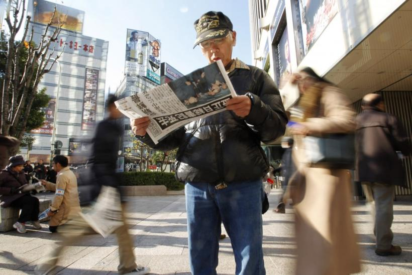 A man reads an extra edition of a newspaper reporting the death of North Korean leader Kim Jong-il, at Tokyo's Ginza shopping district