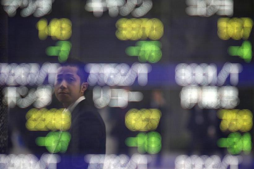 Man is reflected on an electronic board displaying stock prices outside a brokerage in Tokyo