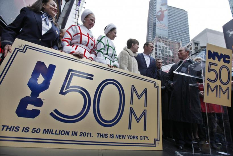 "New York City Mayor Michael Bloomberg presents Craig Johnson and his wife Lucy Johnson from Lichfield England with a ""Golden Ticket"" as the city's honorary 50 millionth visitors for 2011 during a ceremony in Times Square, New York"
