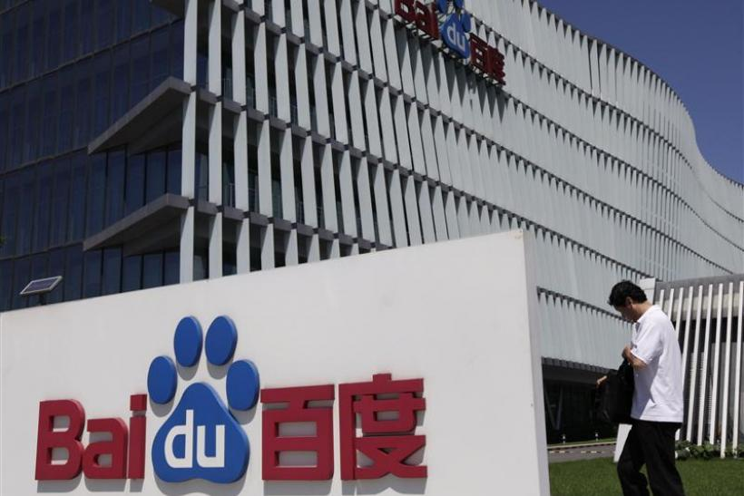An employee walks past the Baidu company signage outside its headquarters in Beijing