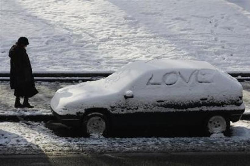 A woman walks by a car covered in snow in Madrid January 11, 2010.