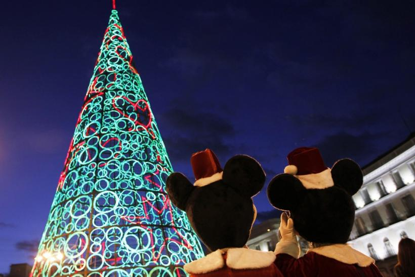 Two people dressed as Mickey Mouse stand next to Christmas tree made out of lights as they wait to perform for children at Puerta del Sol square