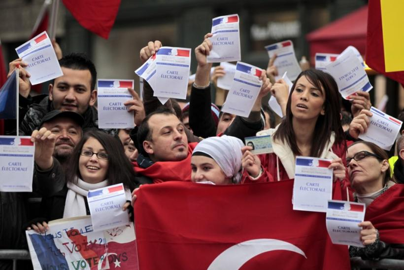 Franco-Turks protesters hold French electoral cards and a Turkish flag as they attend a demonstration next to the National Assembly in Paris