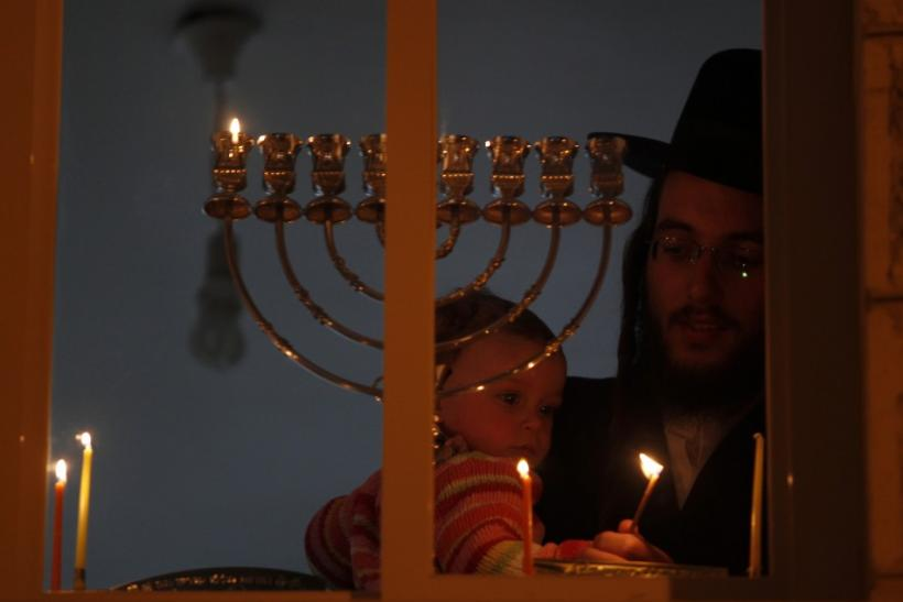 An Ultra-Orthodox Jewish man holds a child as he lights a candle for Hanukkah in Jerusalem's Mea Shearim neighbourhood