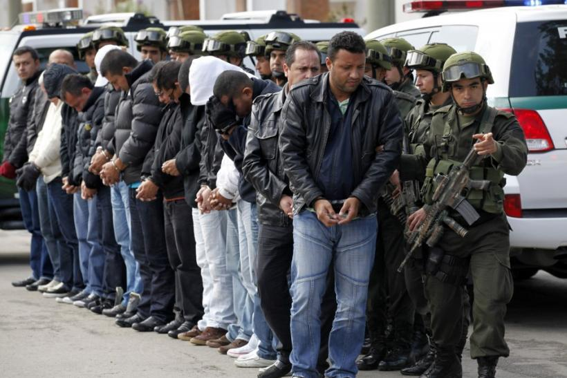 "National Police escort fourteen suspected members of the ""ERPAC"" gang during their presentation to the media in Bogota"