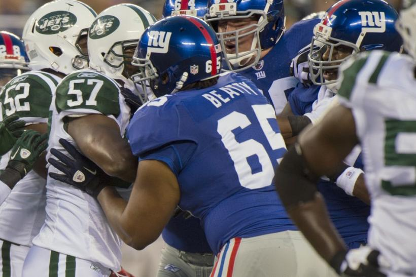 New York Giants Will Beatty and David Diehl separate New York Giants Brandon Jacobs and New York Jets Bart Scott in East Rutherford