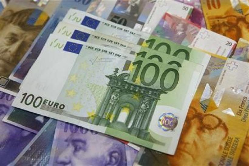 One hundred Euro banknotes lay on top of various Swiss Franc notes in this picture illustration at a bank in Warsaw, July 18, 2011.