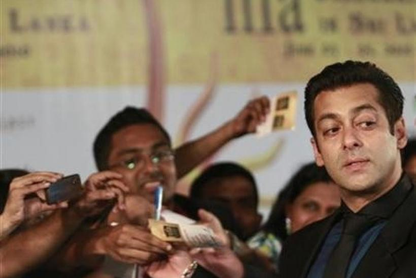 Bollywood actor Salman Khan (R) reacts on the green carpet for the International Indian Film Academy (IIFA) awards in Colombo