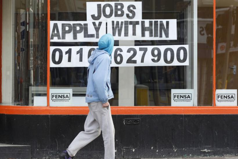 A man walks past a shop advertising job vacancies in Leicester