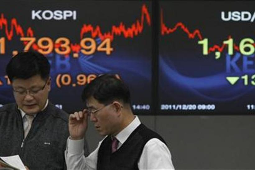 Currency dealers talk in front of screens showing the stock price index and the exchange rate between the South Korean won and the dollar at a bank in Seoul