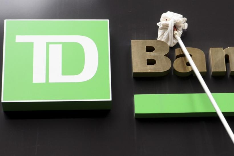 A window washer cleans the sign on a TD Bank in New York's financial district