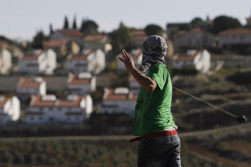 The West Bank Jewish settlement of Halamish is seen in the background as a Palestinian demonstrator uses a sling to throw a stone towards Israeli soldiers during clashes near Ramallah