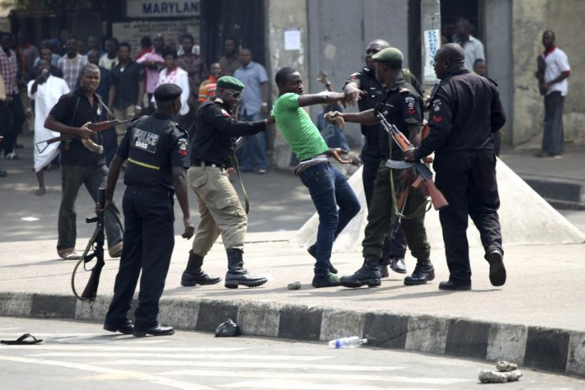 Policemen beat up a protester during a rally against fuel subsidy removal in Lagos