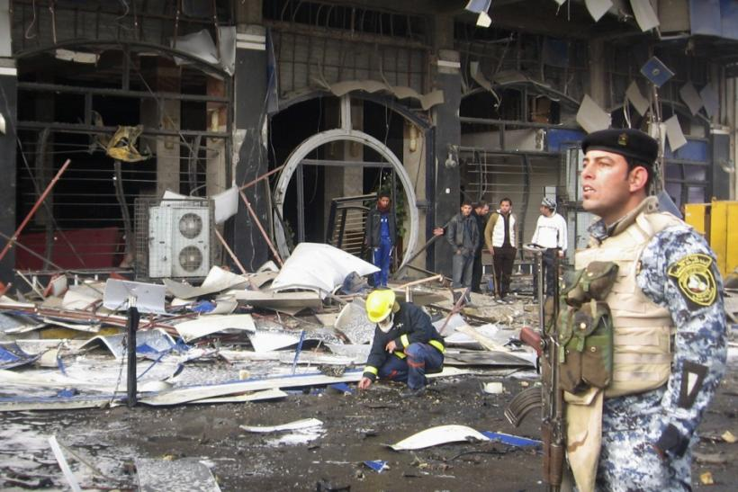 A police officer provides security at the site of a bomb attack in Baghdad's northwestern Kadhimiya district