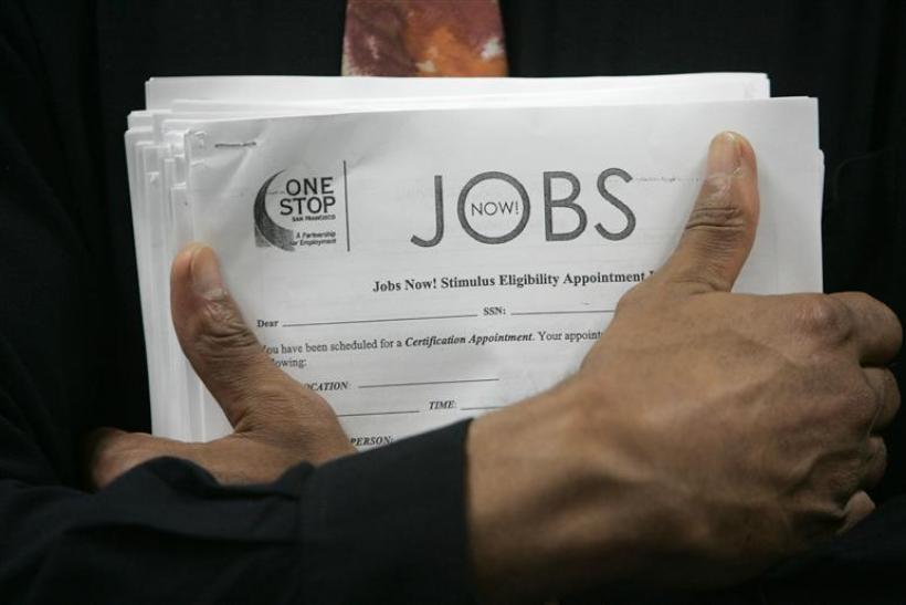 Man carrying a stack of job listings listens to a discussion at the One Stop employment center in San Francisco