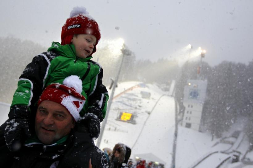 Spectators leave the stadium in heavy snow fall after the qualification for the fourth event of the 60th four-hills ski jumping tournament was cancelled in Bischofshofen