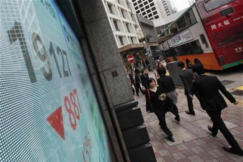 People walk past a panel displaying the blue-chip Hang Seng Index outside a branch of China Construction Bank in Hong Kong