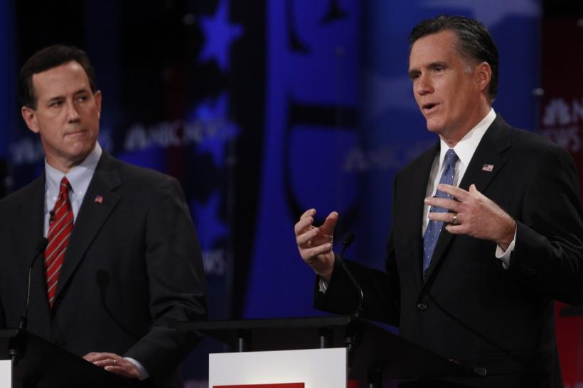 Republican presidential candidates (L-R) former U.S. Senator Rick Santorum (R-PA) listens as former Massachusetts Governor Mitt Romney speaks during the Republican presidential candidates debate in Concord, New Hampshire, January 8, 2012.