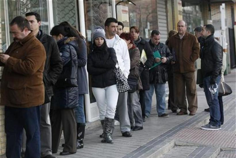 People wait in line for the opening of a government employment office in Madrid