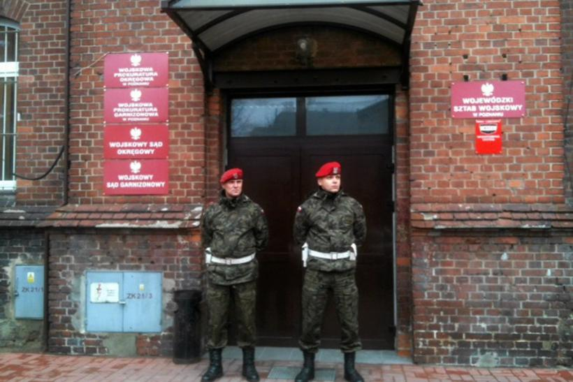 Military police stand guard outside military prosecutor's office in Poznan where military prosecutor Colonel Przybyl attempted suicide by shooting himself in head following news conference