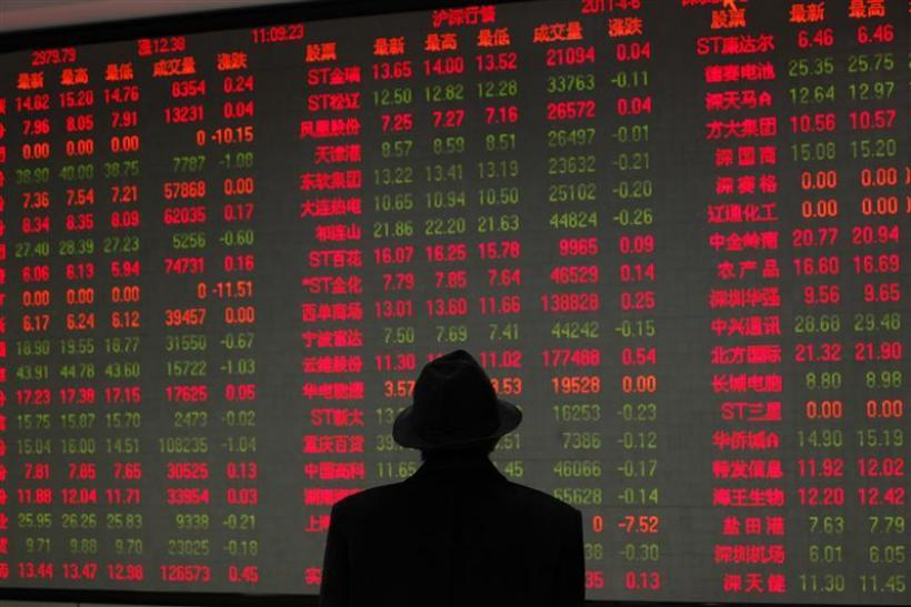A man looks at an electronic board at a brokerage house in Shanghai