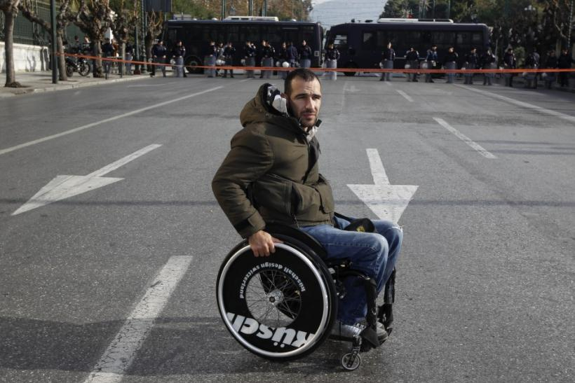 A protester with disabilities is seen in front of a police formation during a protest against austerity measures in Athens