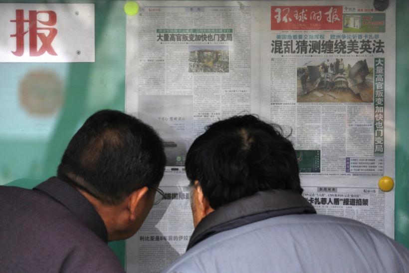 Locals read Chinese newspapers displayed on a public notice board in central Beijing