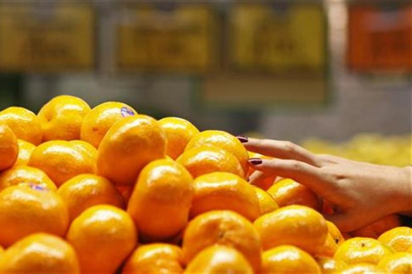 A woman picks up some mandarin oranges at a fruit shop