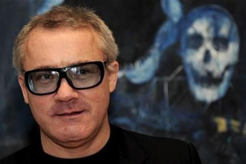 British artist Damien Hirst poses for photographers in front of his painting ''Shark's Jaw, Skull and Iguana on a Table'' (2008), in London