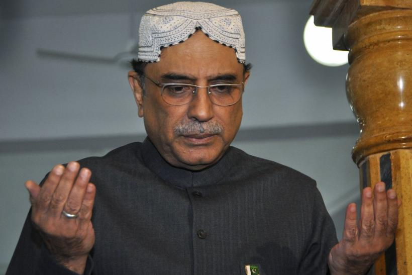 Pakistan's President Zardari, widower of assassinated former PM Benazir Bhutto, raises his hands in prayer at her grave to mark her death anniversary at the Bhutto family mausoleum in Garhi Khuda Bakhsh