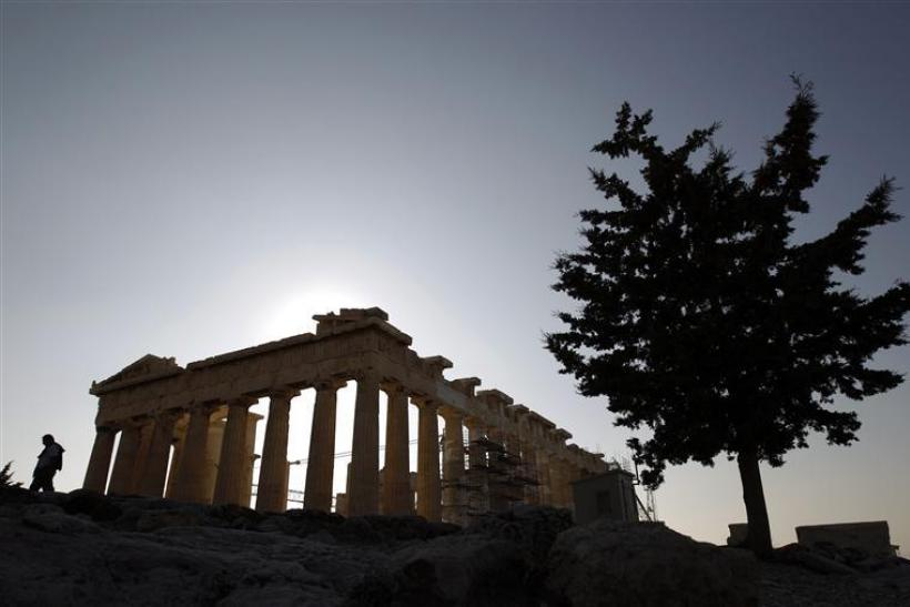 A tourist walks in front of the Parthenon temple at the Acropolis in Athens