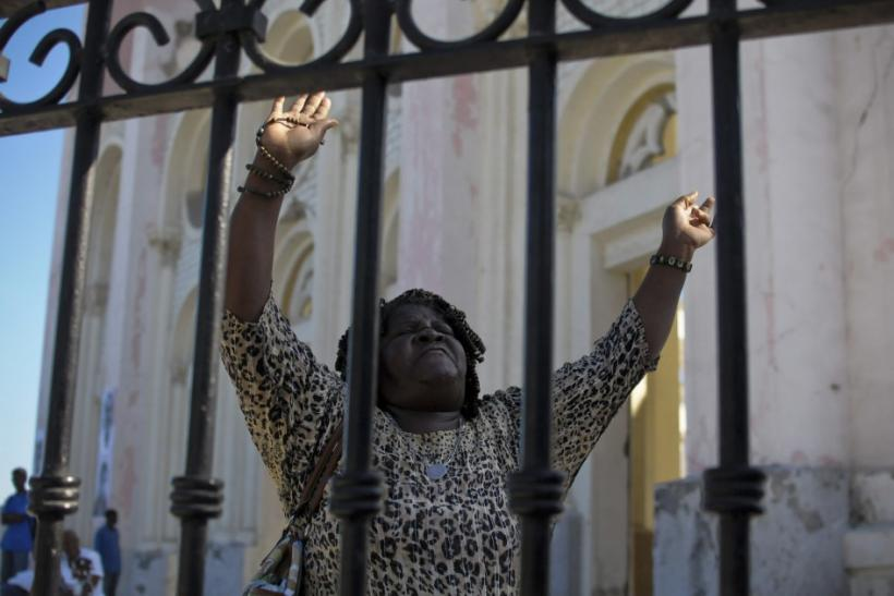 A woman raises her arms while praying outside a destroyed cathedral in downtown Port-au-Prince