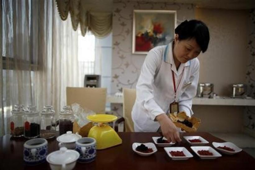 An employee prepares food for mothers using traditional Chinese medicine at the CareBay maternity care centre in Shanghai December 23, 2011.