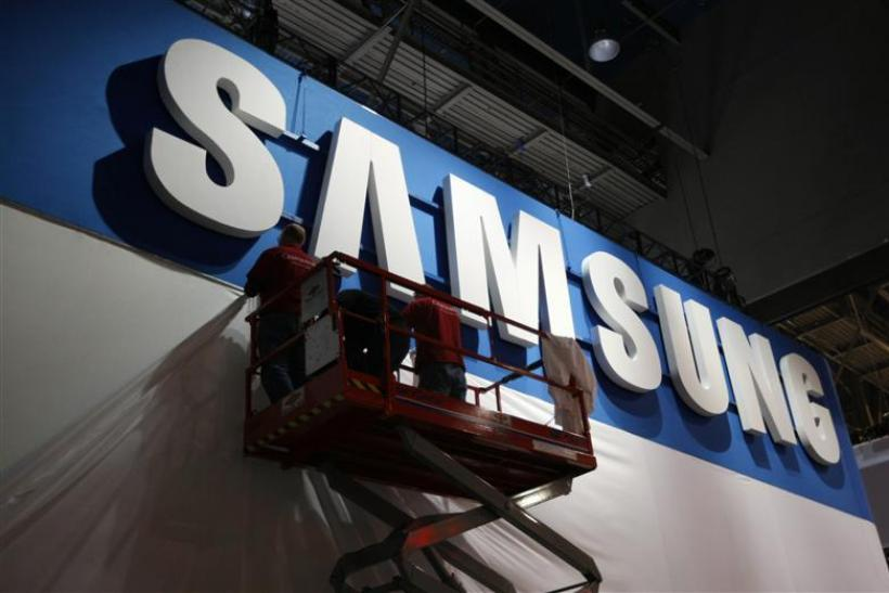 Workers prepare the booth for Samsung at the Consumer Electronics Show opening in Las Vegas