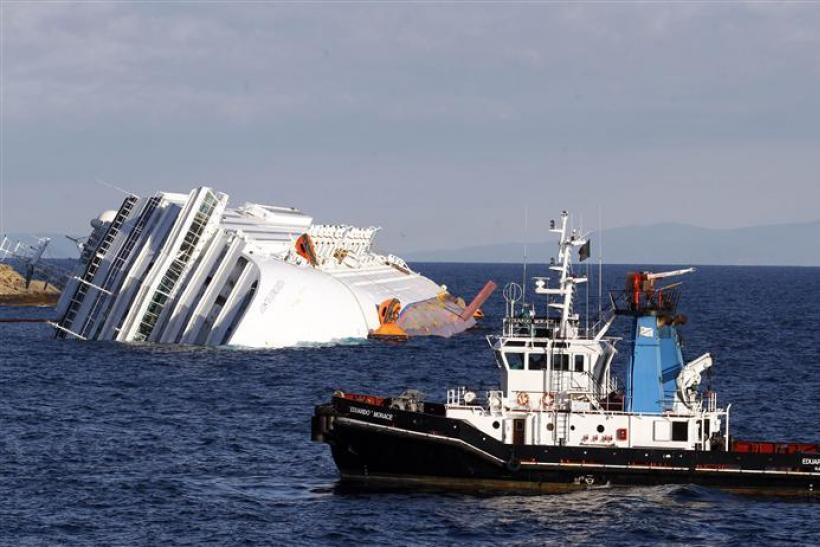 A boat with rescue workers is seen near the Costa Concordia cruise ship that ran aground off the west coast of Italy, at Giglio island