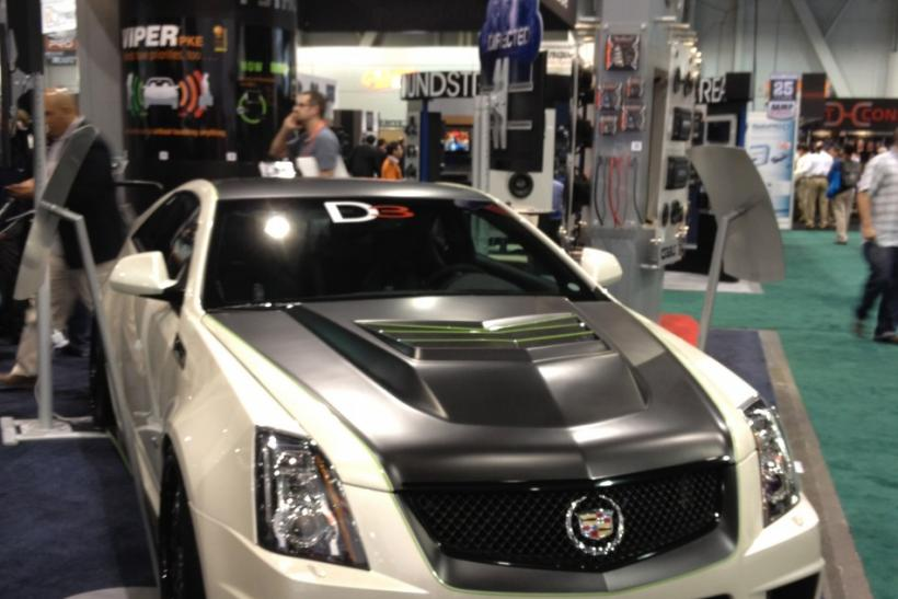 A customized Cadillac features a suped-up hood.