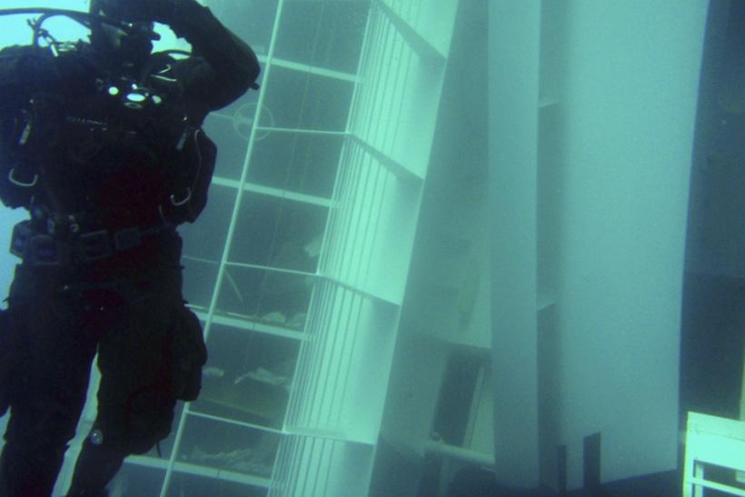 A scuba diver inspects a side of the Costa Concordia cruise ship, seen underwater after it ran aground off the west coast of Italy, at Giglio island